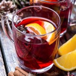 Hot drink, mulled red wine in a cup of glass on a wooden background