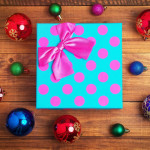 Christmas gift and different christmas toys on wooden background.
