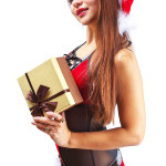 Beautiful and sexy woman in santa clause costume holding a gift
