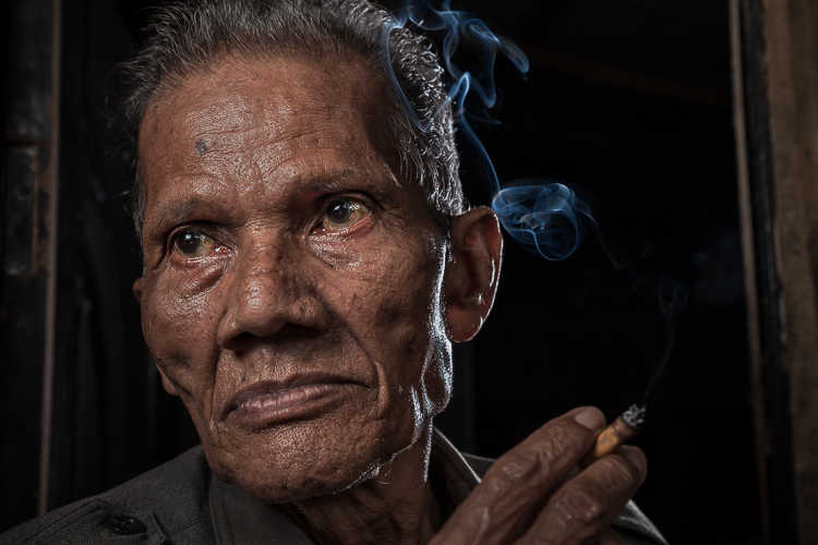 Close-up portrait of Indonesian man smoking in the doorway to his home
